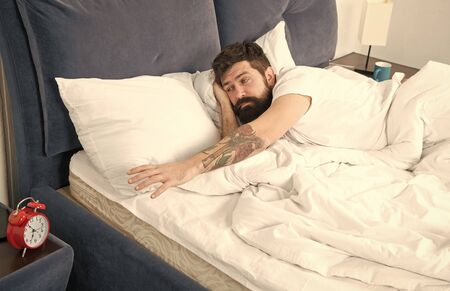 What terrible noise. Problem early morning awakening. Get up with alarm clock. Overslept again. Tips for waking up early. Man bearded hipster sleepy face bed with alarm clock. Turn off that ringing Stockfoto - 129239506