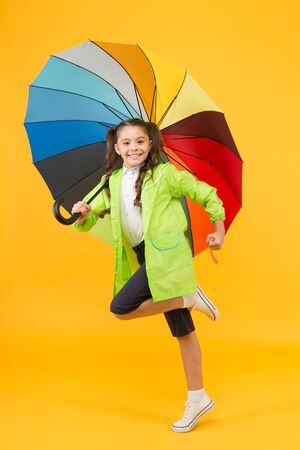 Simple happiness. I do not care. Carefree schoolgirl jumping with umbrella waterproof rain coat. Autumn rain. Rainy days bright accessories. Rain is not so bad if you have water resistant clothes