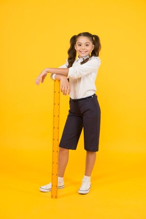 Exploring stem. Geometry school subject. School adorable student study geometry. Kid school uniform hold ruler. Education and school concept. Sizing and measuring. Pupil cute girl with big ruler