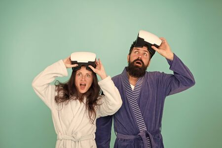 Conscious awakening. Return to reality. Man and woman explore vr. VR technology and future. VR communication. Exciting impressions. Awakening from virtual reality. Couple in bathrobes wear vr glasses 写真素材