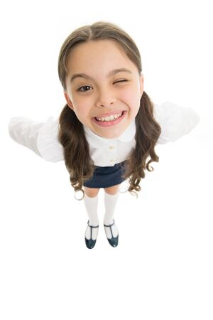 Cheerful smile. Student little kid adores school. Pupil of first grade. Celebrate knowledge day. September time to study. Girl cute pupil on white background. School uniform. Back to school Фото со стока
