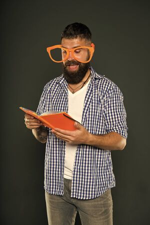He enjoying the stories. Book nerd wearing fancy glasses. Study nerd reading book. University male student holding lecture notes. Bearded man in party glasses with lesson book