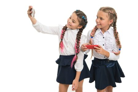 Nurturing your blog culture. Little schoolchildren making selfie for new blog isolated on white. Small bloggers keeping school life blog. Cute girls taking blog photos with smartphones, copy space Reklamní fotografie