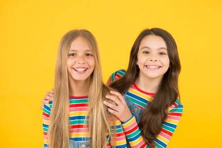 Long hair best female adorn. Girls blonde and brunette shiny healthy hair. Hair strengthening. Grow hair. Hairdresser salon. Kids beautiful friends or sisters with perfect hairstyles. Natural beauty Standard-Bild - 129242865
