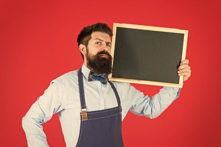 Exclusive cocktail. Hipster restaurant staff. Hipster informing you. Man bearded bartender or cook in apron hold blank chalkboard. Price list concept. Hipster bartender show blackboard copy space