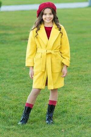Child in warm clothes. Feeling cozy and comfortable. Fancy coat. Classic coat does not have to be boring but sticking to scale of warm, understated tones. Girl fashionable model wear yellow wool coat