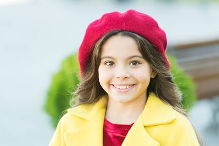 Stunning charisma. Girl adorable kid walk defocused background. Fashionable girl curly hair on sunny autumn day close up. Kid bright hat and warm coat. Adorable face. Adorable baby fashion model Фото со стока
