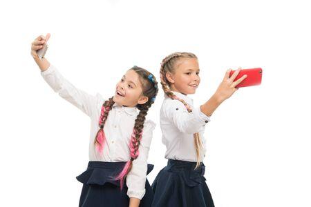 Prawdziwe gwiazdy selfie. Szczęśliwe małe uczennice biorąc selfie ze smartfonami na białym tle. Małe dzieci, uśmiechając się do aparatów selfie w telefonach komórkowych. Cieszę się sesją selfie 1 września