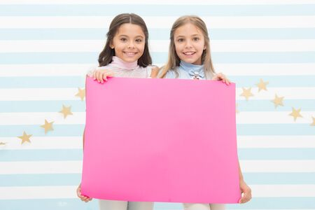 For your text. Happy children holding empty sheet of paper. Little children smiling with pink drawing paper. Small children with blank advertisement poster. Cute children advertising, copy space Standard-Bild