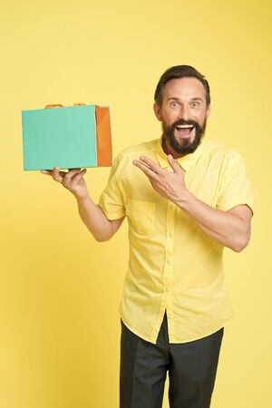 Bearded mature man with shopping bag on yellow background. Sale and discount. Online shopping. Profitable purchase. Shop assistant or sales expert. Shopping happiness. Man emotional enjoying shopping Фото со стока