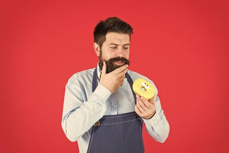Ways to reduce hunger and appetite. Hipster bearded baker hold glazed donut on red background. Cafe and bakery concept. Sweet donut from baker. Man bearded baker in cooking apron hold cute dessert