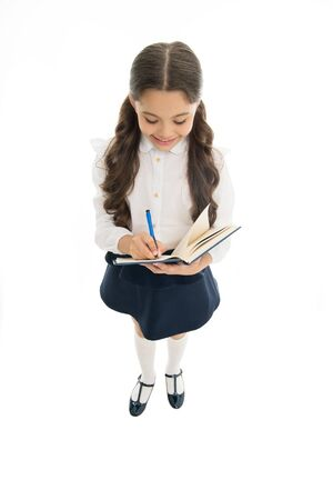 Writing essay. School girl excellent pupil prepared essay or school project. Schoolgirl wear school uniform. Knowledge day. Girl with copy book or workbook. Kid perfect student ready with homework