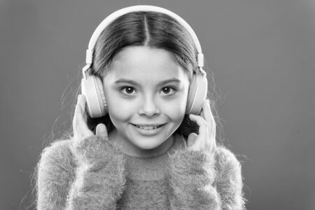 Modern music is her life style and pleasure. Little modern girl wearing wireless headphones. Small child listening to music in everyday life. Using modern technology in daily life. Modern life Stock Photo - 129245712