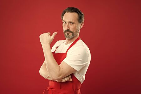 Cooking is passion. Cook with beard and mustache wear apron red background. Man mature cook posing cooking apron. Fine recipe. Ideas and tips. Chief cook and professional culinary. Cook food at home Banque d'images - 129245726