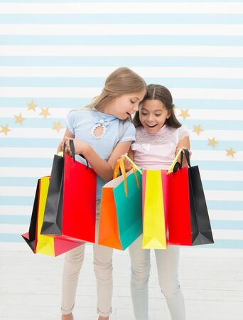 Shopping, the place for fun. Cute little shoppers. Adorable girls looking into shopping bags. Small children enjoy shopping. Shopping for real life