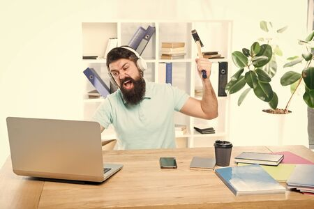 Hate office routine. Man bearded guy headphones office swing hammer on computer. Slow internet connection. Outdated software. Computer lag. Reasons for computer lagging. How fix slow lagging system Stock Photo
