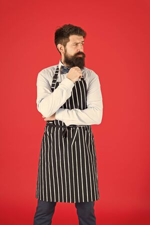 Man with beard cook hipster apron. Hipster chef cook red background. Bearded man chef cooking. Restaurant staff and service. Well groomed waiter at work. Hipster cafe concept. On duty in kitchen