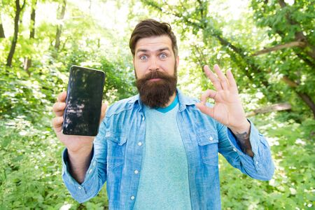 Hiking with navigation app. Route for exciting adventure. GPS and navigation apps. Useful program. Smartphone online navigation. Man bearded wanderer walking in forest with navigation application