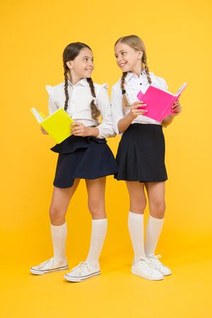 As the Page Turns. little girls in school uniform. reading story. childrens literature. kids learning grammar. back to school. dictionary notebook. Get information. cheerful classmates with workbook