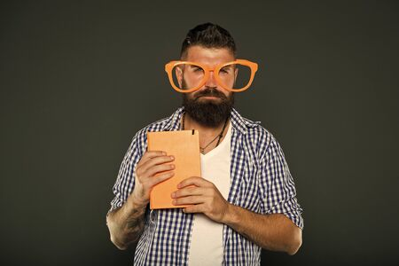 Geek is chic. Study nerd holding book. University male student with lecture notes. Book nerd wearing fancy glasses. Bearded man in party glasses with lesson book