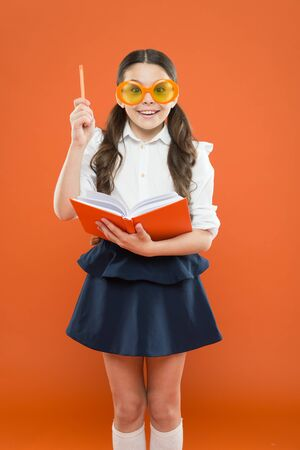 Happy little schoolgirl ready for lesson. Cute child with book. Only wisdom knowing you know nothing. Study foreign language. Study literature. Pupil likes study. Small girl enjoying her school time 写真素材