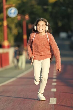 Towards happy day. Girl cute with headphones. Little child enjoy activity. Kid walking running in park listening music. Music fills me with energy. Enjoy walk with favorite music in headphones