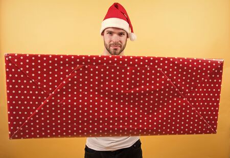 Christmas gift concept. Santa bring gift for you. Man attractive santa claus carry big box. You deserve good gift. Christmas holiday celebration. Man handsome unshaven santa hat hold gift box Standard-Bild