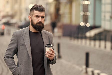 Man bearded hipster drink coffee paper cup. Businessman well groomed enjoy coffee break outdoors urban background. Prefer coffee on the go. Thoughtful but relaxed. Take self care. Delicious drink