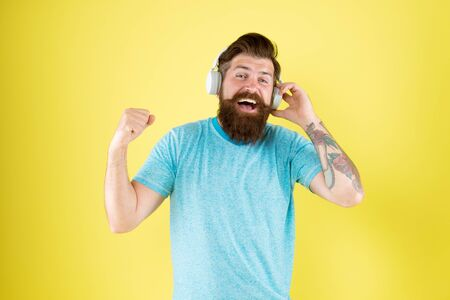 Bearded man listen music wireless gadget. Hipster happy using modern wireless headphones. Freedom going wireless offers you is unparalleled. Wireless headphones deliver clean sound. Modern technology Foto de archivo - 129246153
