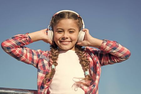 True hapiness. Small music fan. Happy small girl. Small girl listen to music outdoor. Happy child wear headphones. Bring music to life