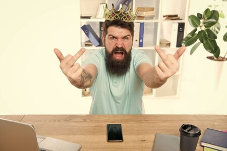 Go to hell. Aggressive boss shouting show middle finger gesture. Man arrogant rude boss with golden crown sit in office. Superiority and self confidence. King of office. Serious boss at work place Stock Photo - 129246212