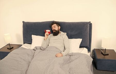 Tips for waking up early. Man bearded sleepy face bed with alarm clock in bed. What terrible noise. Turn off that ringing. Problem early morning awakening. Get up with alarm clock. Need more sleep Stockfoto - 129246227