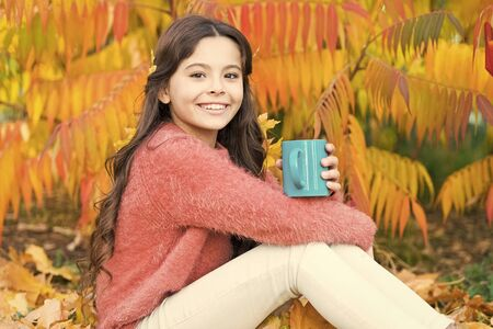 I have a wonderful childhood. Little child enjoy autumn hot drink. Little child relax at autumn tree. Happy childhood years. Lucky to play up in trees Imagens