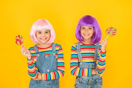 Anime cosplay party concept. Happy little girls. Anime fan. Kids with artificial hairstyles eating lollipops. Anime convention. Vibrant characters fantastical themes. Modern childhood. Childrens day Stock Photo