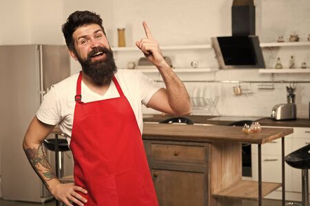 Need culinary inspiration. How to turn cooking at home into habit. Man bearded hipster red apron stand in kitchen. Kitchen furniture store. Cooking in new kitchen. Weekend begins from tasty breakfast
