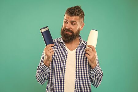 Man bearded hipster choose shampoo or shower gel. Hair care and skin treatment. Choose beauty product. Barbershop and hair care. Wash hair with shampoo. Hair conditioner or lotion. Make right choice