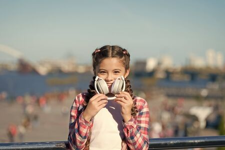 Benefits of foldable headphones. Foldability makes it more portable. Best foldable and portable headphones. Girl little kid hold foldable headphones while walk outdoors. Modern music gadget