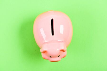 income management. planning budget. financial problem. piggy bank on green background. money saving. top view of money box. empty moneybox. moneybox with slot. you have nothing