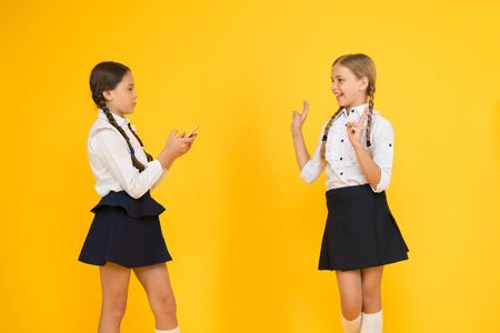 School application smartphone. Schoolgirls use mobile phone or smartphone to share photos. Internet is wonderful resource but access to it has hazards for kids. Girls school uniform using smartphone