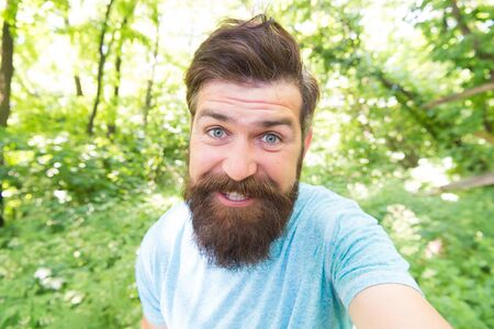 Beard can make a man look more brutal. Happy man with long mustache and beard hair outdoor. Brutal man smiling with unshaven face and stylish haircut. Bearded man in casual style on natural landscape