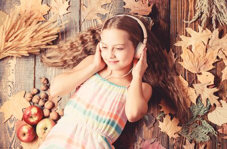 Getting into an autumnal mood. Adorable music fan on autumn background. Little girl listening to music in headset. Small girl wearing stereo headphones. Cute child enjoy music playing in earphones Stock Photo