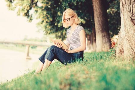 Such an interesting book. inspired by novel author. interesting story. Relax and get new information. reading is my hobby. Summer study. student girl with book outdoor. woman in park reading book