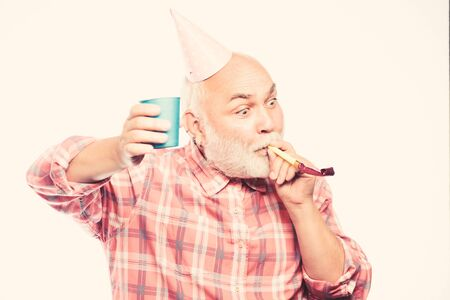 Elderly people. Man bearded grandpa with birthday cap and drink cup. Birthday crazy party. Ideas seniors birthday celebrations. Grandfather graybeard blowing party whistle. Getting older is still fun