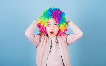 Circus school concept. Acting school for children. Develop acting talent into career. Girl artistic kid practicing acting skills. Kid colorful curly wig artificial hair clown style blue background
