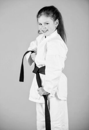 small girl in martial arts uniform. little girl in gi sportswear. practicing Kung Fu. happy childhood. knockout. energy and activity for kids. sport success in single combat. Having a little break