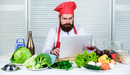 Man chef searching internet recipe cooking food. Chef laptop read culinary recipes. Culinary school. Hipster in hat and apron learning how to cook online. Culinary education online. Elearning concept