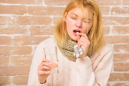 Girl suffer fever and take medicine. Headache and fever remedies. What to know about breaking fever. Take medications to reduce fever. Woman tousled hair scarf hold glass water and tablets blister