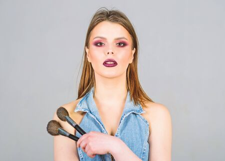 Makeup dark lips. Attractive woman applying makeup brush. Professional makeup supplies. Hiding imperfections. Makeup artist concept. Girl apply powder eye shadows. Looking good and feeling confident Zdjęcie Seryjne - 129253383
