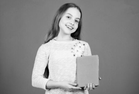 Shes a student of language and literature. Cute little child holding book in English literature. Adorable small girl reading literature book. Fiction and scientific literature, copy space