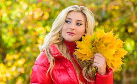 Woman spend pleasant time in autumnal park. Lady posing with leaves autumnal nature background. Girl blonde makeup dreamy face hold bunch fallen maple yellow leaves. Autumnal bouquet concept